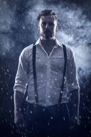 movie poster: Young man   rocker with ear rings standing in the snow with smoke in the background   Stock Photo