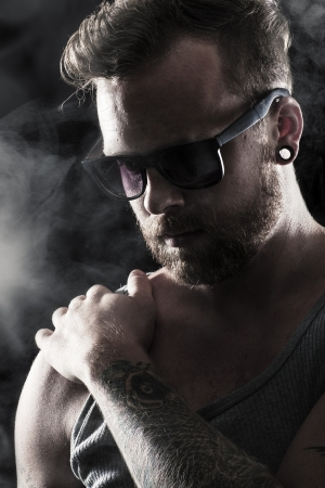Young man   rocker with sunglasses, tattoos and ear rings  Smoke and scene light  photo