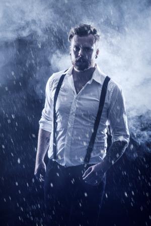 Jonge man rocker met oor ringen die in de sneeuw met rook in de achtergrond