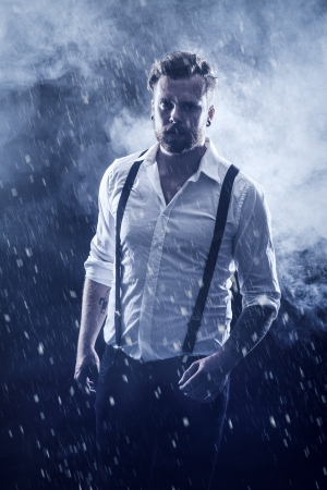 Young man   rocker with ear rings walking in the snow with smoke in the background   photo