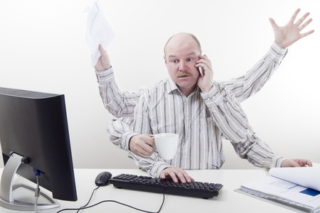 Busy and multitasking office worker with arms all over in the office  To much work  Stock Photo