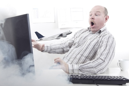 A Plane flying out of a Office workers computer monitor  Order vacation   holiday   plane tickets on internet Stock Photo - 19199994