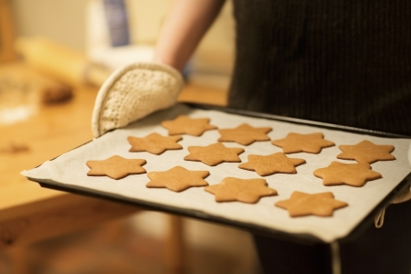 baking tray: Woman baking ginger bread stars for Christmas  Natural Colors  Real life