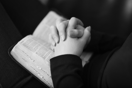 A black and white close-up of a christian woman folding hands and praying on the bible  Shot with Canon 85mm 1 2L  Very shallow depth of fields