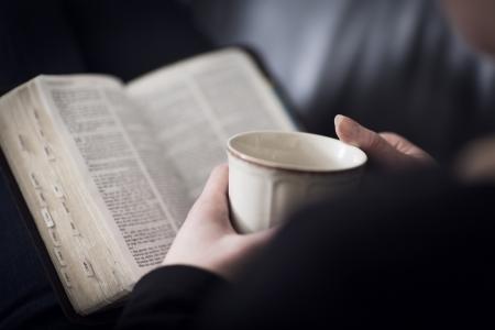 mujer leyendo libro: Un primer plano de una mujer de la lectura y estudio de la Biblia cristiana en muy poca profundidad de campo virada