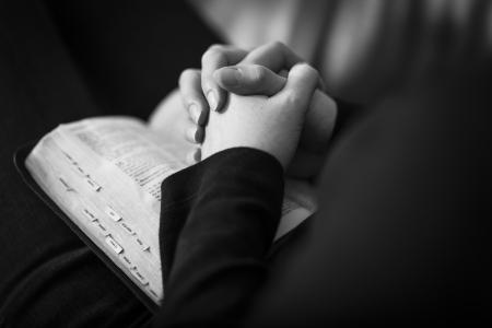 vangelo aperto: Un primo piano di una donna cristiana mani pieghevoli sulla Bibbia e pregare Girato con 85 mm 1 2L Molto poca profondit� di campo