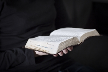holding bible: A close-up of a christian woman reading and study in the bible  Very shallow depth of fields  Toned  Stock Photo
