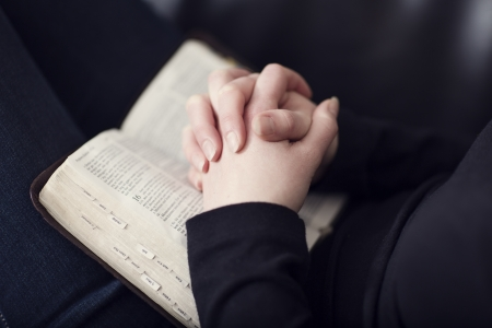 A close-up of a christian woman folding hands on the bible  Shot with 85mm 1 2L  Very shallow depth of fields  Toned  Stock Photo