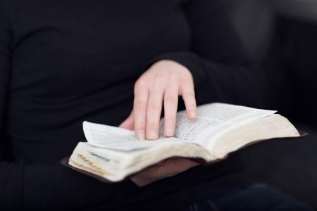 vangelo aperto: Un primo piano di una lettura donna cristiana e lo studio della Bibbia profondità Molto di campi Tonica Archivio Fotografico
