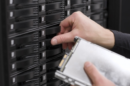 It engineer   technician working in a data center  This enclosures is a SAN  storage area network  and servers bellow  Stock Photo