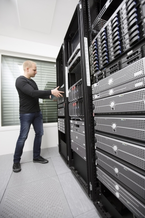 server side: It engineer   consultant wokring and install   inserts a router   switch in a data rack  Shot in a data center