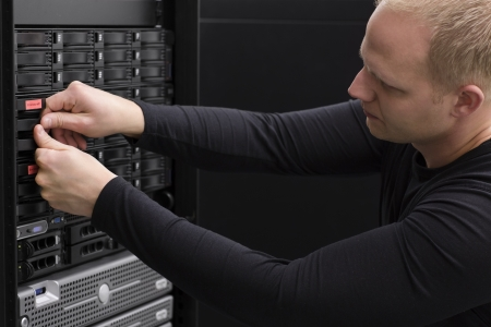 enclosures: It engineer   technician working in a data center  This enclosures is a SAN  storage area network  and servers bellow  Stock Photo