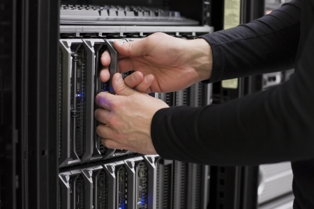 it technician: IT technician   engineer install   removes   replace a blade server in a data center  Stock Photo