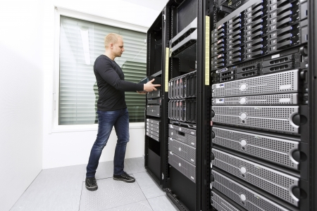 It engineer   consultant wokring and install   inserts a router   switch in a data rack  Shot in a data center