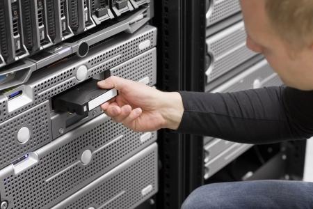 Ein IT-Techniker Ingenieur Berater legen Sie eine Backup-Band in einem Backup-Roboter in einem Rack in einem Rechenzentrum mit Blade-Servern und Festplattengehäuse Schuss Standard-Bild