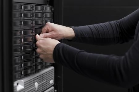 bellow: Es ingeniero t�cnico que trabaja en un centro de datos Cajas Industriales es una red de �rea de almacenamiento SAN y los servidores de abajo Foto de archivo