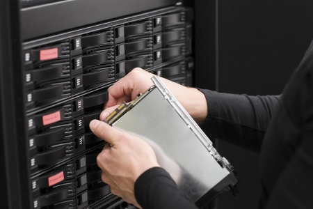 It engineer   technician working in a data center  This enclosures is a SAN  storage area network  and servers bellow  photo