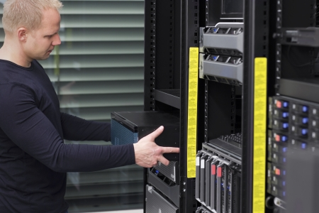 inserts: It engineer   consultant install   inserts a router   switch in a rack  Shot in a data center