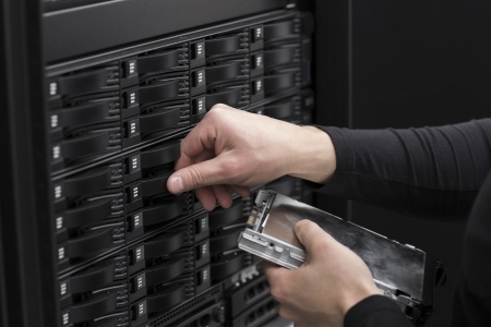 hard drive: It engineer   technician working in a data center  This enclosures is a SAN  storage area network  and servers bellow  Stock Photo