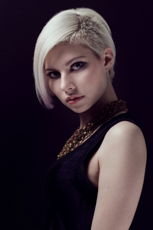 A low key photo of a beautiful and glamorous young woman with creative hair style  Colored and natural retouched  photo