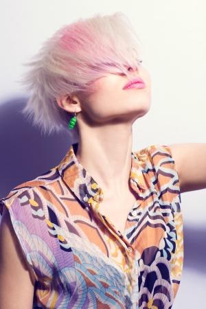 Eine junge Frau mit kreativen Frisur und 1980er Jahren aussehen Hard Licht in Farbe