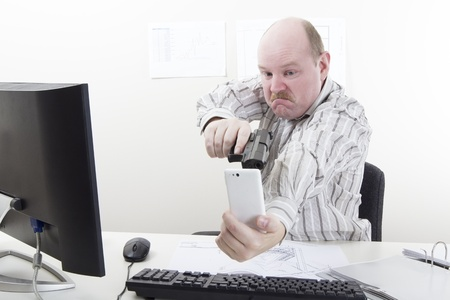 office physical pressure paper: Man points a gun at his mobile   cell phone in his office