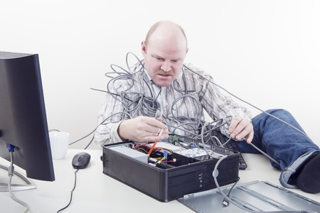 Office worker   businessman in cables has computer problems