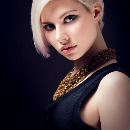 A low key photo of a beautiful and glamorous young woman with creative hair style photo