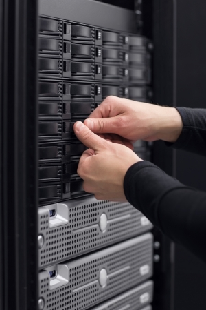 it technician: It engineer   technician working in a data center  This enclosures is a SAN  storage area network  and servers bellow  Stock Photo
