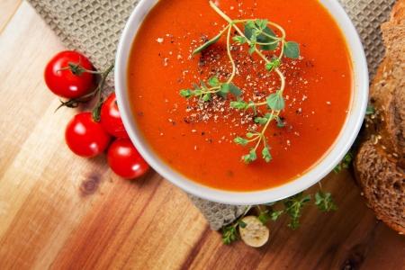 Frischer Gourmet Tomatensuppe mit frischen Kräutern und Pfeffer Brot, Oregano und Tomaten auf der Seite Standard-Bild