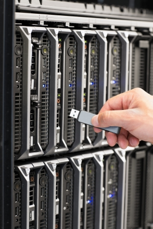 IT technician installs and maintain a blade servers in a data center  Plugs in a flash drive  photo