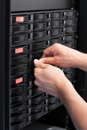 It engineer   technician working in a data center  Replace a hard drive in a SAN  photo