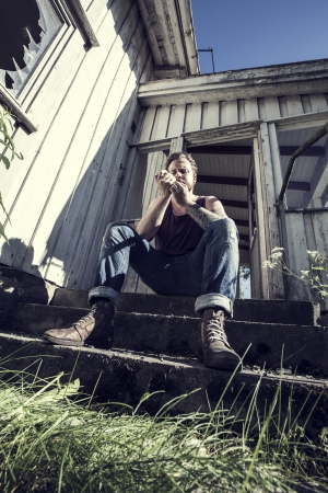 A young man sitting outside a abandoned house and lighten up a smoke  photo