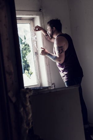 Rocker standing by a broken window, smoking cigarettes and thinking  photo