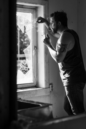 broken window: Rocker standing by a broken window, smoking cigarettes and thinking  Stock Photo