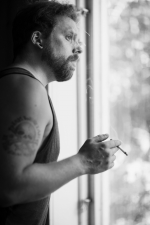 Punk rocker standing by the window, smoking cigarettes and thinking  photo