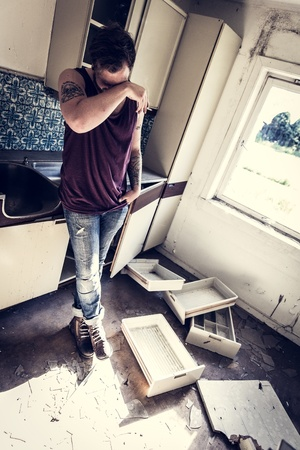 messy kitchen: A young and exhausted redneck   rocker with hangover