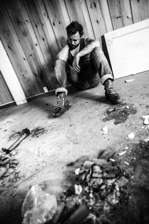 messy house: Punk rocker or redneck sits on the floor and think in messy house  Stock Photo