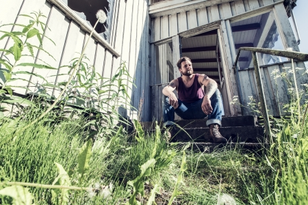 A young man sitting outside abandoned house and smoke cigarettes  photo