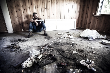 Man or redneck sits on the floor and smoke in a messy house  photo