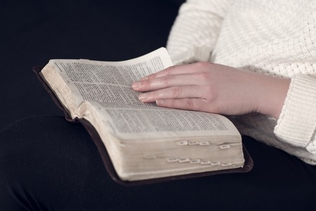 Girl reading the holy bible at home  Sitting in sofa  photo