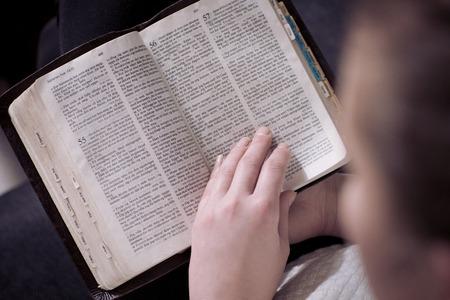 自宅で聖書を読むキリスト教の女の子はソファに座ってください。
