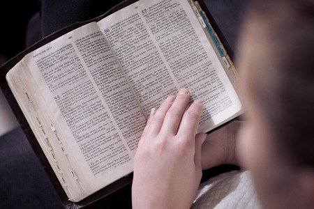Christian girl reading the holy bible at home  Sitting in sofa  Stock Photo