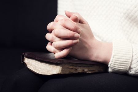 Woman folding hands over her holy bible and praying to God  photo