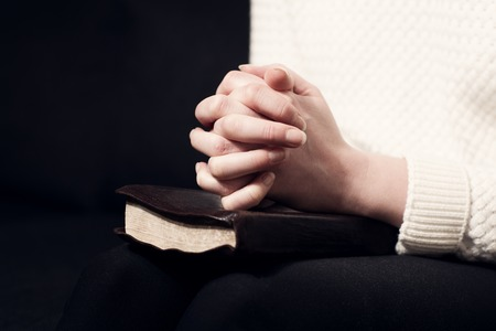 adulation: Woman folding hands over her holy bible and praying to God