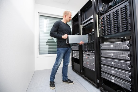 It engineer or consultant working with installation of a blade server in data rack  Shot in datacenter