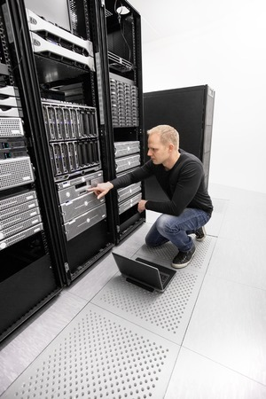 It engineer or consultant working with backup server. Shot in data center. photo