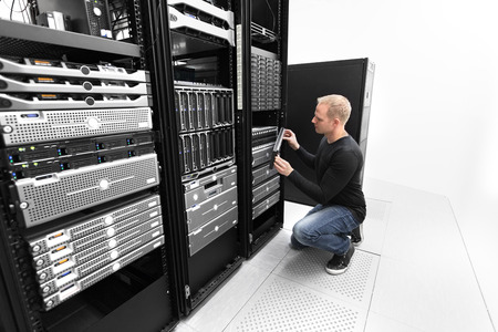 server side: It engineer or consultant maintaning storage area network SAN in data rack. Shot in datacenter.