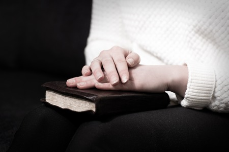 non moving activity: Woman holding hands over her bible and praying to God
