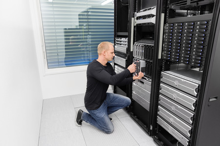 It engineer or consultant working with installation of a blade server in data rack. Shot in datacenter. photo